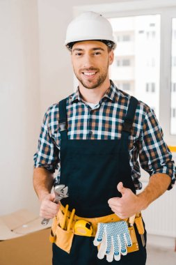 cheerful handyman holding wrench and showing thumb up