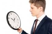 pohledný podnikatel při pohledu na hodiny izolované na bílém