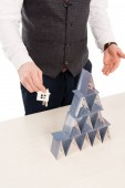 Fotografie cropped view of real estate agent holding house keys and showing pyramid from playing cards, isolated on white
