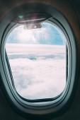 Fotografie Flugzeugfenster mit blauem, sonnigen Blick auf den Himmel