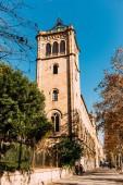 Barcelona, Španělsko – 28. prosince 2018: ulice s zelenými stromy a vysoké staré věže na pozadí modré oblohy