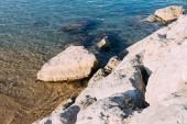 Fotografie clear transparent sea water and coast rocks, barcelona, spain