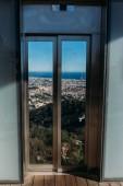 okno s výhledem na malebné město na úpatí zelených kopců, barcelona, Španělsko