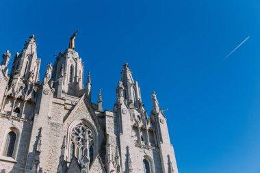 exterior of temple expiatori del sagrat on blue sky background, barcelona, spain