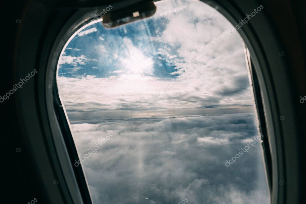 airplane porthole with beautiful cloudy sky view