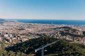 Fotografie scenic view of city on foot of green hills and blue sea, barcelona, spain