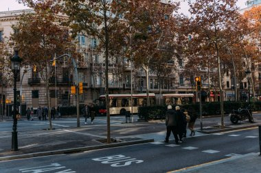 BARCELONA, SPAIN - DECEMBER 28, 2018: busy street with people crossing road and boulevard with trees stock vector