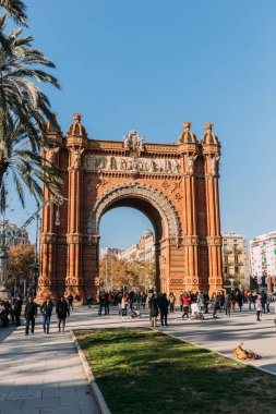 BARCELONA, SPAIN - DECEMBER 28, 2018: Arc de Triomf, famous city landmark, and people walking along wide alley stock vector