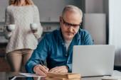 szelektív összpontosít, koncentrált ember írás közelében laptop feleségével a cups háttér gazdaság szemüveg