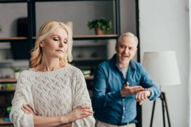 selective focus of woman standing with crossed arms while husband arguing on background