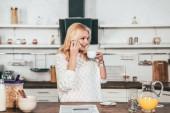 Veselá žena mluvila na smartphone při pití kávy v kuchyni