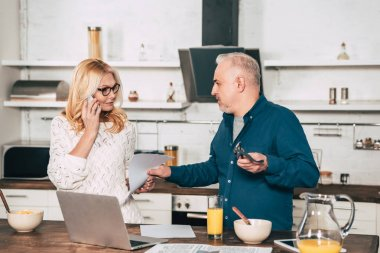 attractive woman talking on smartphone and standing with husband in kitchen near laptop