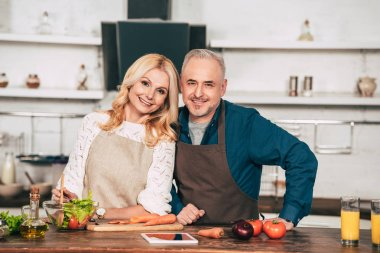 happy woman smiling while standing with husband in kitchen
