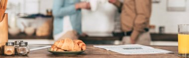 selective focus of croissants on plate near glass of orange juice with couple on background