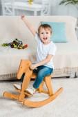 rozkošný vzrušený preschooler chlapce na houpacím koni a ukázal rukou doma