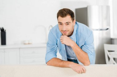 Handsome smiling man propping chin with hand, leaning on sofa and looking at camera at home stock vector