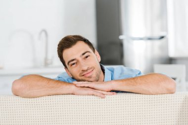 handsome smiling man looking at camera and leaning face on hands at home