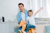 Šťastný otec při pohledu na fotoaparát zároveň vzrušený preschooler syn jezdecké dřevěné houpací koně doma