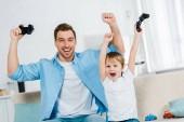 Aufgeregter Vater und Vorschulsohn jubeln beim Videospiel zu Hause mit den Händen in der Luft