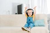entzückende männliche Kleinkind in Kopfhörer mit den Händen in der Luft Musik hören zu Hause mit Kopierraum