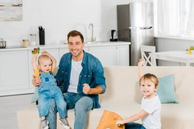 happy father looking at camera while spending time and playing with cheering preschooler and toddler sons in apartment