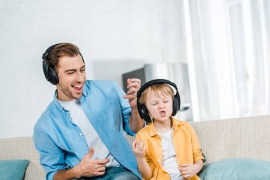 father with preschooler son in headphones listening music, gesturing with hands and playing imaginary guitars at home