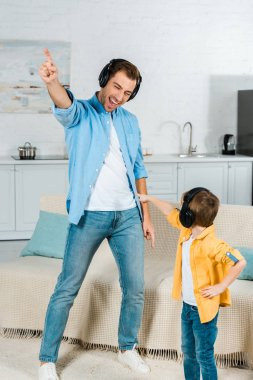 happy father with preschooler son in headphones listening music and pointing with fingers at home