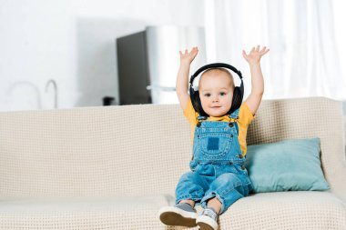 adorable male toddler in headphones with hands in air looking at camera and listening music at home