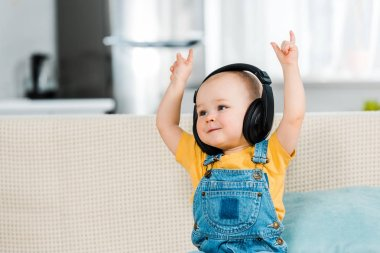 adorable male toddler in headphones listening music and showing rock signs at home