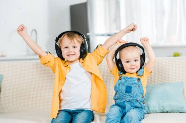 adorable brothers in headphones looking at camera and cheering with hands in air at home