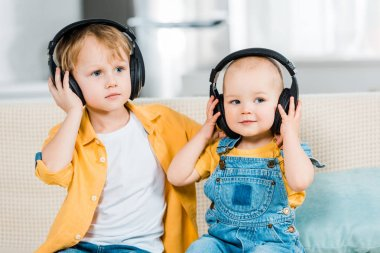 adorable brothers listening music in headphones at home