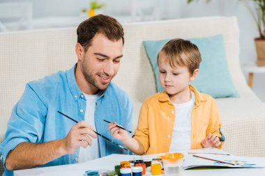 smiling father and preschooler son holding paintbrushes and drawing at home