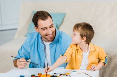 happy father and preschooler son holding paintbrushes and drawing at home