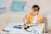 roztomilý preschooler chlapec kreslení štětcem doma