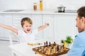 Vorschulsohn jubelt mit den Händen in der Luft, während er zu Hause mit dem Vater Schach spielt