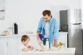 Fotografie handsome father pouring cereal in bowl while preschooler son drawing during breakfast in morning