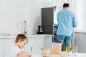 Fotografie preschooler son drawing during breakfast with father on background in kitchen