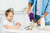 Fotografie father pouring cereal in bowl while smiling preschooler son drawing during breakfast in morning