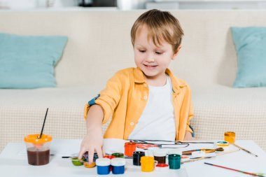 adorable smiling preschooler boy picking up paints during drawing at home