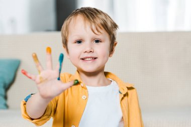 adorable smiling preschooler boy with colorful paint on hand looking at camera at home