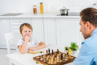 preschooler son picking nose while playing chess with father at home