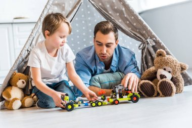 Father and preschooler son playing with toy cars and teddy bears under wigwam at home stock vector