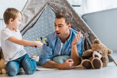 surprised father looking at preschooler son playing with toy car under wigwam at home