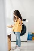 gyermek állandó és kosár fedél tartja a mosodában