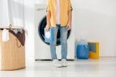 Fotografie verkürzte Ansicht des Kindes im gelben Hemd und Jeans mit Waschpulver in Waschküche