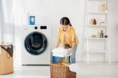 Fotografie Kind in gelbem Hemd neben Waschmaschine und Leiter legt Handtücher in Korb in Waschküche