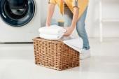 Fotografie abgeschnittene Ansicht des Kindes in der Nähe der Waschmaschine, die Handtücher in den Korb in der Waschküche legt
