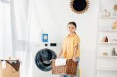 Kind in der Nähe der Waschmaschine hält Korb mit Handtuch in der Waschküche