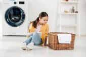 Kind in gelbem Hemd und Jeans sitzt mit digitalem Tablet und sucht Korb in Waschküche