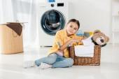 Kind in gelbem Hemd und Jeans sitzt neben Korb mit Bärenspielzeug in Waschküche